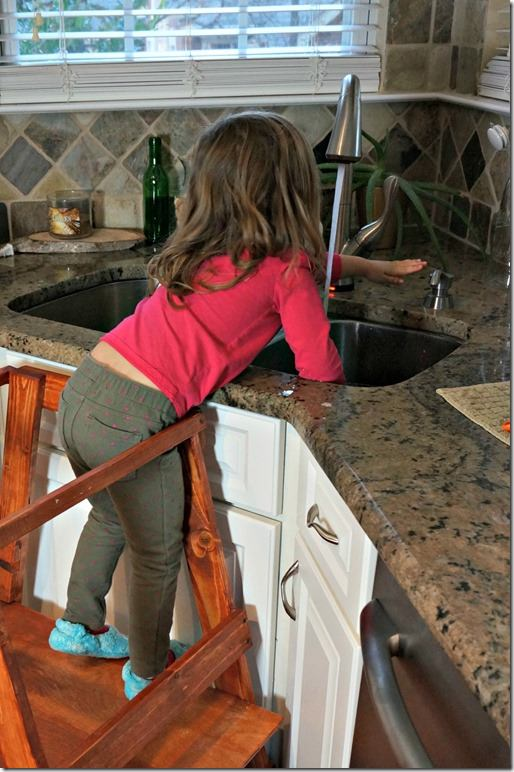 three year old washes her hands