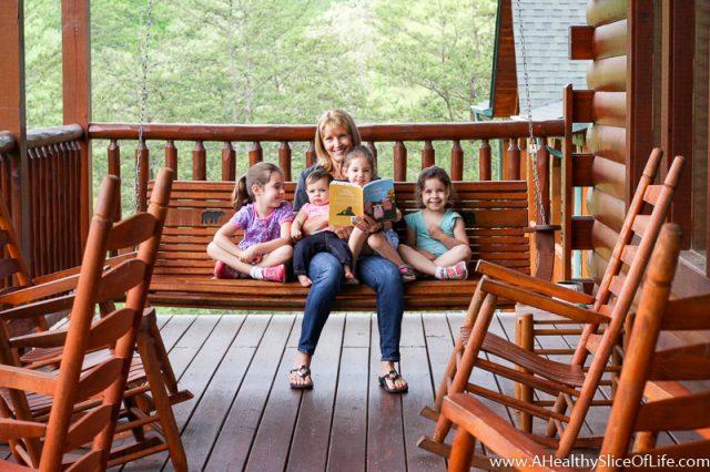 nana reading to girls on porch