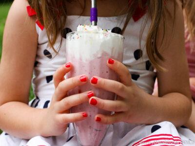 little girl holding milkshake